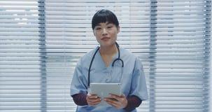 Jonge vrouwelijke arts gebruikend tablet en sprekend aan camera 4k stock videobeelden