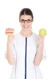 Jonge vrouwelijke arts, verpleegster die een appel houden en doughtnuts. Stock Afbeeldingen