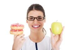Jonge vrouwelijke arts, verpleegster die een appel houden en doughtnuts. Stock Foto