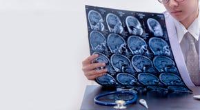 Jonge vrouwelijke artsenholding MRI of CT aftastenbeeld stock foto's