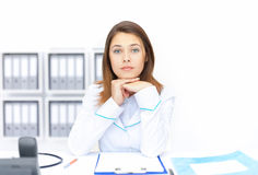 Jonge vrouwelijke artsenzitting bij bureau in het ziekenhuis Stock Fotografie