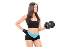 Jonge vrouwelijke atleet die met een barbell uitoefenen Stock Foto's
