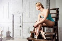 Jonge vrouwelijke balletdanser bindende linten op hun Pointe stock afbeelding