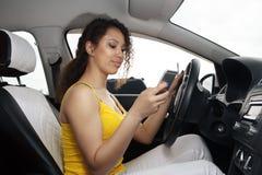 Jonge vrouwelijke bestuurder die smartphone van het aanrakingsscherm en gps navigatie in een auto gebruiken stock foto's