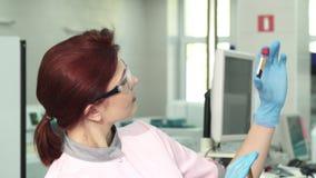 Jonge vrouwelijke bioloog die twee reageerbuizen met bloed onderzoeken stock video