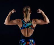 Jonge vrouwelijke bodybuilder met perfect sterk spierlichaam die sportkledingsbovenkledij het stellen op zwarte achtergrond drage royalty-vrije stock fotografie
