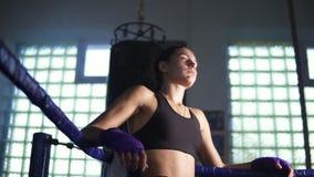 Jonge vrouwelijke bokser die aan de hoek van de boksring komen en rustend met haar wapens op de ringskabels in de donkere gymnast stock footage