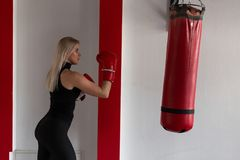 Jonge vrouwelijke bokser in rode bokshandschoenen in motie om een ponsenzak te raken Het meisje leidt in de gymnastiek op Het in  stock foto's