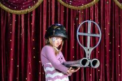 Jonge Vrouwelijke Clown die in Helm Groot Geweer streven Royalty-vrije Stock Foto's