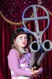 Jonge Vrouwelijke Clown die in Helm Groot Geweer streven Stock Foto's