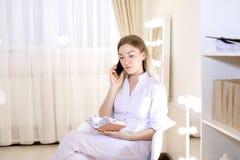 Jonge vrouwelijke cosmetologist die door smartphone bij kabinet spreken Stock Fotografie