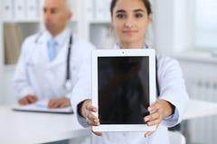 Jonge vrouwelijke de aanrakingsstootkussen of tablet van de artsenholding met exemplaarruimte Reclame in geneeskunde royalty-vrije stock fotografie