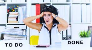 Jonge vrouwelijke die beambte door de reusachtige hoeveelheid administratie wordt geschokt Uiterste termijnconcepten stock fotografie