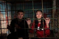 Jonge vrouwelijke en mannelijke die slachtoffers in een holding van de metaalkooi worden gevangengenomen stock foto's