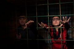 Jonge vrouwelijke en mannelijke die slachtoffers in een metaalkooi reachin worden gevangengenomen royalty-vrije stock fotografie