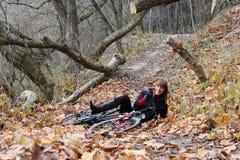 Jonge vrouwelijke fietsruiter die neer glimlacht Royalty-vrije Stock Afbeelding