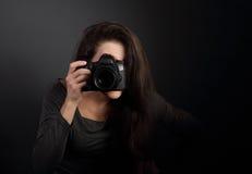 Jonge vrouwelijke foto die de foto op donkere greep maken als achtergrond Royalty-vrije Stock Afbeeldingen