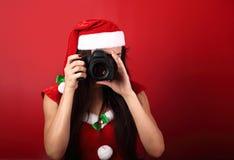 Jonge vrouwelijke foto die de foto op rode holdi maken als achtergrond Stock Afbeeldingen