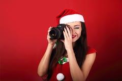Jonge vrouwelijke foto die de foto op rode holdi maken als achtergrond Stock Fotografie