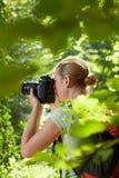 Jonge vrouwelijke fotograaf die in bos wandelt stock afbeelding