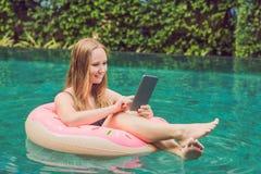 Jonge vrouwelijke freelancerzitting dichtbij de pool met haar laptop in het hotel die in haar smartphone doorbladeren Bezig bij v Stock Afbeelding