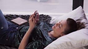 Jonge vrouwelijke het gebruiken smartphone op bed door venster stock footage