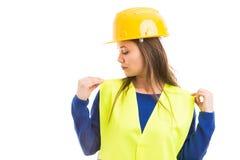 Jonge vrouwelijke ingenieur die haar vest aanpassen stock foto