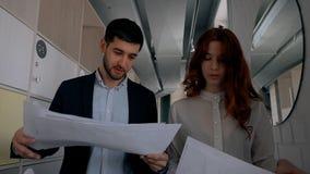 Jonge vrouwelijke intern met rood haar die financiële grafieken tonen aan haar mannelijke werkgever stock video