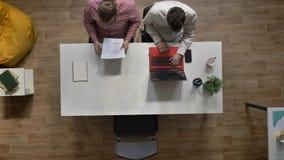 Jonge vrouwelijke kandidaat die voor baangesprek binnenkomen, het schudden handen met werkgevers, die in modern bureau zitten, to stock videobeelden