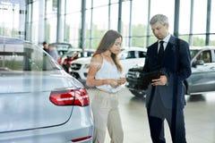 Jonge vrouwelijke klant die rijpe afdelingschef vragen om in het autohandel drijven te helpen royalty-vrije stock afbeelding