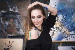 Jonge vrouwelijke kunstenaar die abstract beeld in studio schilderen, mooi sexy vrouwenportret Stock Foto
