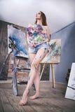 Jonge vrouwelijke kunstenaar die abstract beeld in studio schilderen, mooi sexy vrouwenportret Royalty-vrije Stock Fotografie