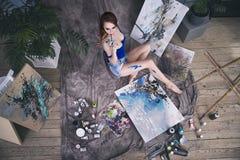 Jonge vrouwelijke kunstenaar die abstract beeld in studio schilderen, mooi sexy vrouwenportret Royalty-vrije Stock Foto's