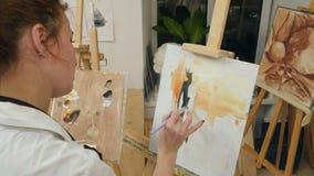 Jonge vrouwelijke kunstenaar in schort het schilderen met olie op wit canvas stock videobeelden