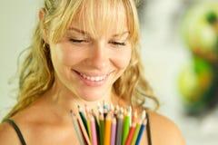 Jonge vrouwelijke kunstenaarsholding kleurpotloden en het glimlachen Stock Foto's