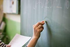 Jonge vrouwelijke leraar of een student het schrijven wiskundeformule op bord Stock Afbeeldingen