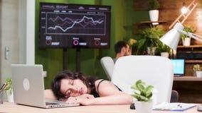 Jonge vrouwelijke managerslaap bij de baan stock footage