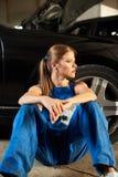 Jonge vrouwelijke mechanische zitting dichtbij de zwarte auto stock afbeelding