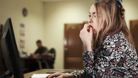 Jonge vrouwelijke medewerker bij haar bureau die aan de computer op het kantoor werken stock footage