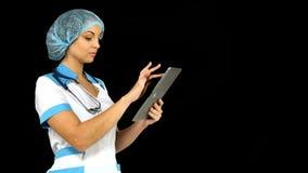 Jonge vrouwelijke medische verpleegster die tabletcomputer met behulp van stock videobeelden