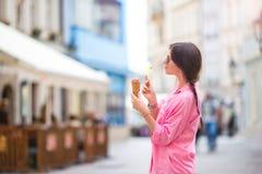 Jonge vrouwelijke model het eten roomijskegel in openlucht De zomerconcept - woamn met zoet roomijs bij hete dag Royalty-vrije Stock Fotografie