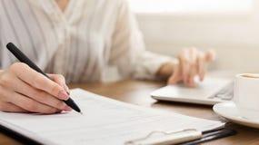 Jonge vrouwelijke ondernemer op laptop en het schrijven nota's stock foto's