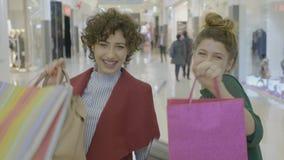 Jonge vrouwelijke ondernemers die hun geluk uitdrukken door het winkelen zakken aan camera te tonen na het kopen van nieuwe kledi stock footage