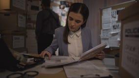 Jonge vrouwelijke onderzoeker die deskundige bevindingenresultaten, vrouwen in politie onderzoeken stock footage