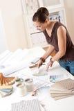 Jonge vrouwelijke ontwerper die met kleurenmonsters werkt Stock Afbeelding