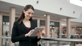 Jonge vrouwelijke passagiersreiziger bij de luchthaven die haar tabletcomputer met behulp van terwijl daarna het wachten op vluch Stock Foto's