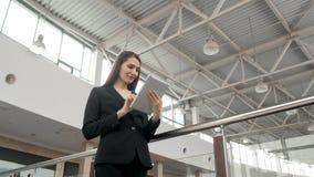 Jonge vrouwelijke passagiersreiziger bij de luchthaven die haar tabletcomputer met behulp van terwijl daarna het wachten op vluch Stock Afbeeldingen