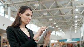 Jonge vrouwelijke passagiersreiziger bij de luchthaven die haar tabletcomputer met behulp van terwijl daarna het wachten op vluch Stock Foto
