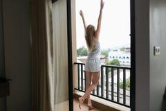 Jonge vrouwelijke persoon die de zomerpyjama's dragen die zich op balkon bevinden en gebouwen met opgeheven handen bekijken Royalty-vrije Stock Foto's