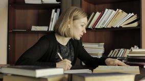 Jonge vrouwelijke Ph D treft voor een lezing voorbereidingen, zittend bij het bureau en schrijft de noodzakelijke informatie van  stock videobeelden
